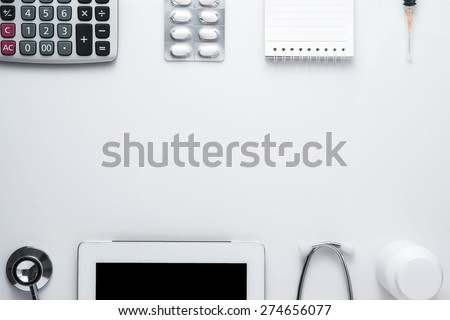 Modern medicine workplace with digital tablet, notepad, stethoscope, calculator, bottles, pills and syringes at doctor's desk. Copy space view from the top - stock photo