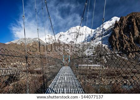 Modern metal bridge in Manang, Himalaya, Nepal - stock photo