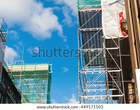 Modern metal scaffolding under blue sky, new building facade under construction - stock photo