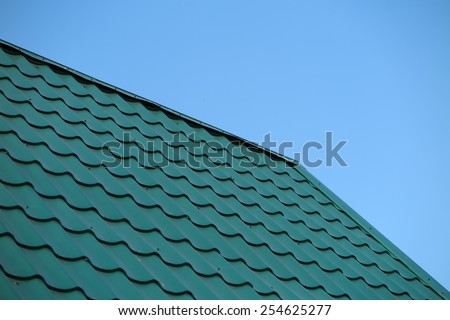 Modern metal tile roofing against a blue sky - stock photo