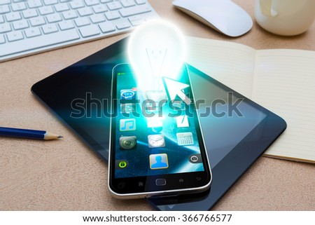 Modern mobile phone in office with lightbulb flying over - stock photo