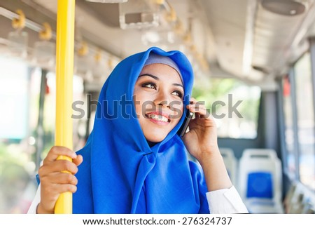 Modern muslim woman in a bus talking on mobile phone - stock photo