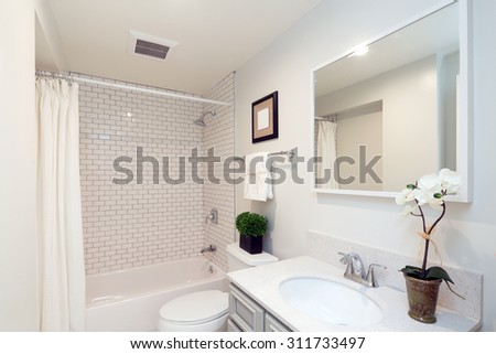 Modern new white small bathroom interior with rectangle mirror and bath tub. - stock photo