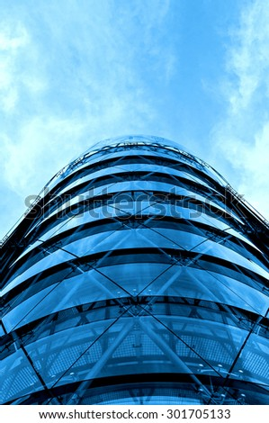 Modern office building with blue glass facade and the blue sky - stock photo