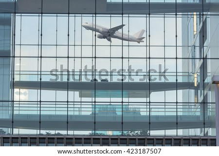 Modern office building with glass facade in the background a plane when you start. - stock photo