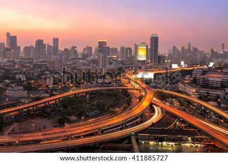 Modern office buildings, condominium in big city downtown with Motorway, Expressway, Freeway the infrastructure for transportation in modern city, urban view at twilight time - stock photo