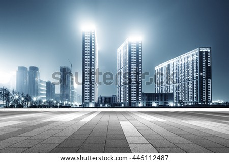 modern office buildings in hangzhou west lake square at night on view from empty street - stock photo