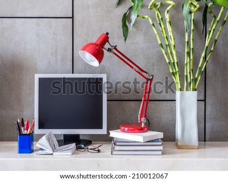 Modern office desk with computer, lamp and vase of Lucky bamboo - stock photo