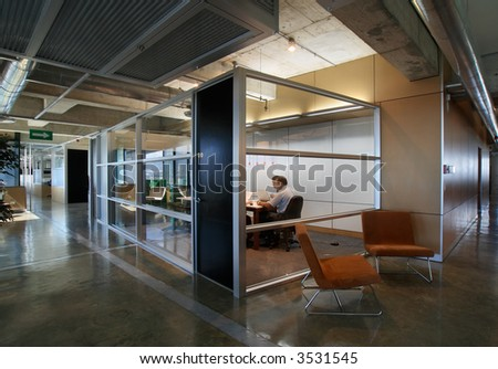 Modern office interior with separate (semi-private) meeting room with glass walls - stock photo
