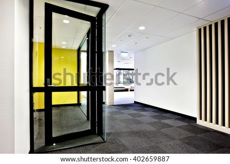 Modern office or apartment area through the hallway with glass doors opened and lights on - stock photo