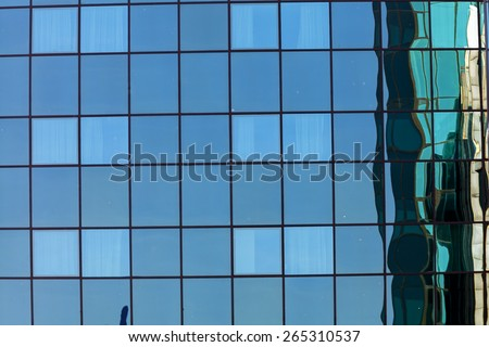 Modern office skyscraper with blue and green glass facade - stock photo