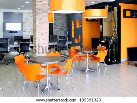 Modern office space with bright orange furniture - stock photo