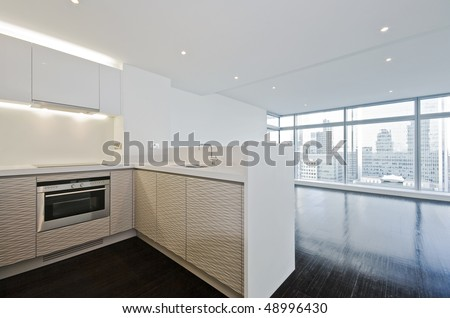 modern open plan kitchen with wooden floor throughout and floor to ceiling windows - stock photo