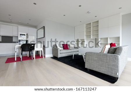 Modern open plan living area with fully fitted kitchen, dining table for four and two large contemporary sofas and glass top coffee table - stock photo