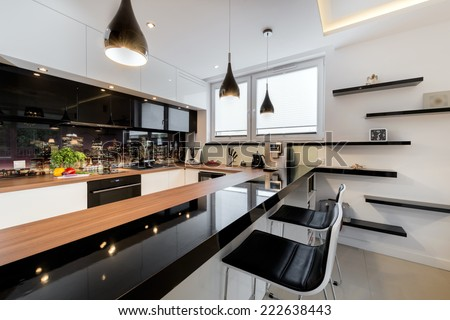 Modern open space luxury kitchen in black and white design - stock photo