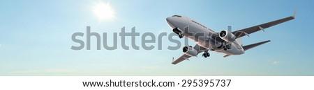 Modern Passenger airplane in flight - panorama - stock photo