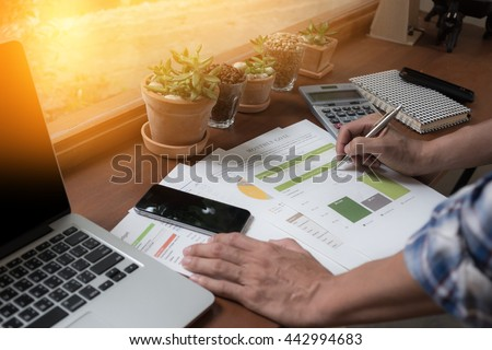 Modern people doing business, graphs and charts being demonstrated on wooden desk in office. - stock photo