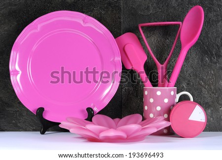 Modern Pink Polka Dot Kitchen with large platter plate, cutlery and kitchenware against black slate and white benchtop. - stock photo