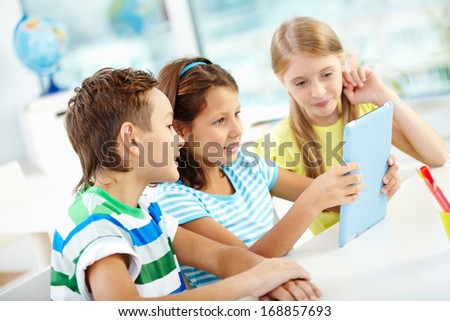 Modern pupils doing their homework with the help of a tablet computer - stock photo