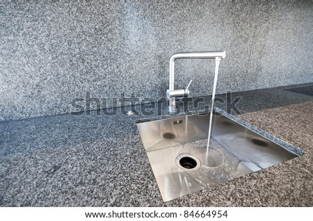 modern rectangular stainless steel kitchen sink on a granite worktop - stock photo