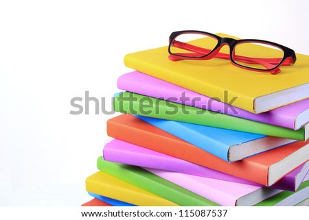Modern red and black fashion eye glasses and colorful books isolated on white background - stock photo