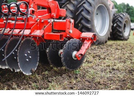 modern red tractor in the agricultural field; mechanism. - stock photo