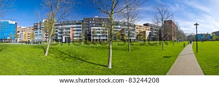 modern residential area of Amsterdam. Park with green grass and trees on the background of modern arhitecture. XXL size. Panorama - stock photo