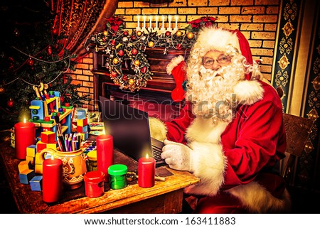Modern Santa Claus sitting with a laptop at his home. Christmas. - stock photo