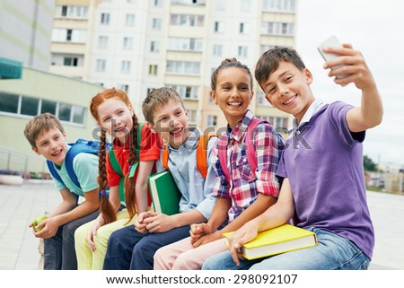 Modern school learners making selfie outside - stock photo