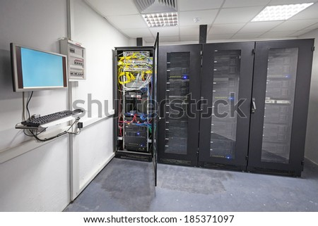 Modern server room interior with black computer cabinets and user terminal on the wall - stock photo