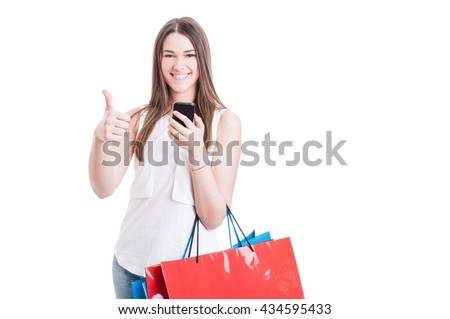 Modern shopping woman with colored paper bags using mobile phone and thumb up isolated on white background with text area - stock photo