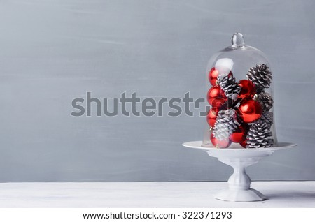 Modern simplistic minimalist christmas table display with pine cones and red baubles under a glass dome - stock photo