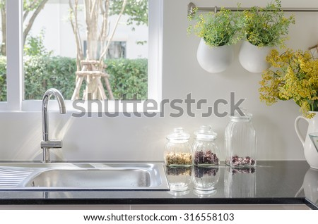modern sink on black kitchen counter with vase of plant - stock photo