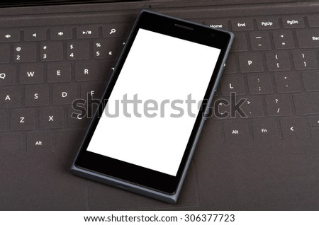 Modern smart cell phone on flat keyboard, business concept - stock photo
