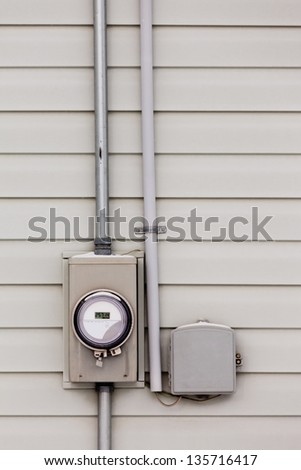 Modern smart grid residential digital power supply meter beside telecommunication connection box on exterior wall - stock photo