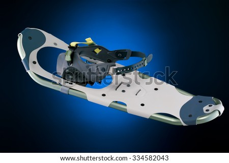 Modern snowshoe top view isolated on gradient black and blue background - stock photo