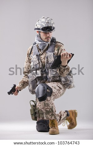 Modern soldier with handgun and tablet computer - stock photo