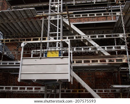 Modern sophisticated scaffolds on a house building under extensive renovations - stock photo