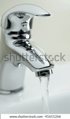 Modern stainless steel tap in kitchen - stock photo