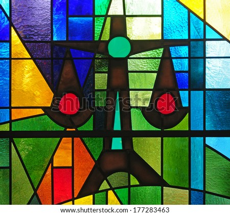 Modern strained glass window depicting scales of justice within colorful abstract design as symbol of social justice - stock photo