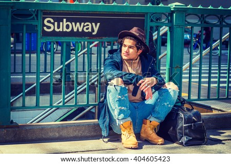 Modern Street Fashion in New York. Wearing blue jacket with hood, jeans, yellow boot shoes, Fedora hat, black leather bag on ground, guy with freckle face, curly hair, sitting on street by Subway sign - stock photo