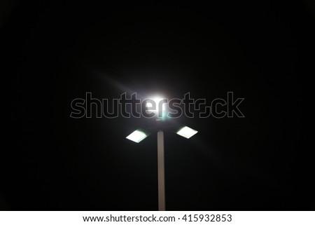 Modern street lights illuminated at night against a dark sky - stock photo