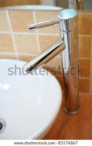 Modern style chrome bathroom tap in modern bathroom. - stock photo
