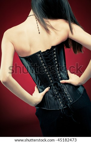 Modern style gothic woman in black leather corset on red vampire background. Hands on waist, standing back to camera. - stock photo