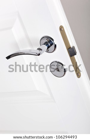 Modern style silver door handle on white door - stock photo