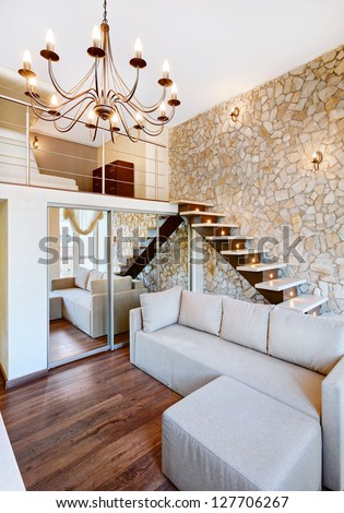 Modern style two-high living-room interior with staircase and stone wall - stock photo