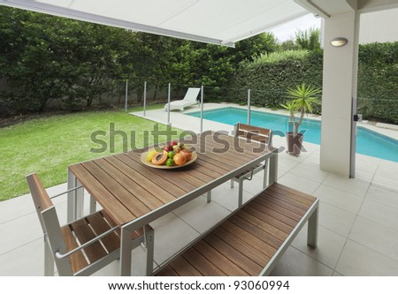 Modern suburban backyard with table setting and swimming pool - stock photo