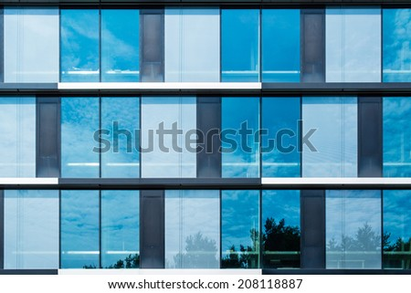 Modern suburban low rise office building with the sky reflecting in great summer sun - stock photo