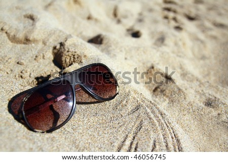 Modern sunglasses on sand - stock photo