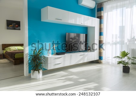 Modern sunny living room with TV and view into the bedroom - stock photo